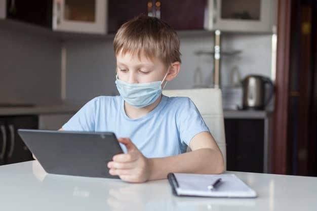 schoolboy-medical-mask-dresses-home-does-homework-home-boy-looks-tablet-back-school-distance-learning-online-education_168258-67